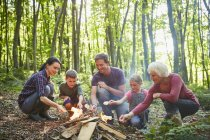 Multi-generation family roasting marshmallows at campfire in forest — Stock Photo