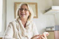 Улыбающаяся пожилая женщина в свитере переписывается с телефоном на кухне — стоковое фото