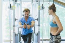 Personal trainer guiding man using cable exercise machine at gym — Stockfoto