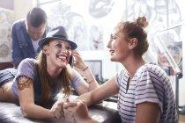 Donna sorridente con amico come tattoo studio — Foto stock