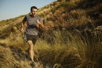 Mann läuft auf Spur durch hohe Gräser — Stockfoto