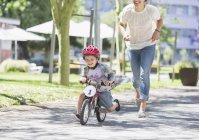 Mère chassant son fils à vélo avec casque dans un parc ensoleillé — Photo de stock