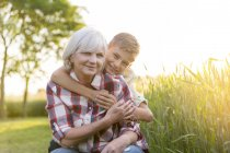 Portrait smiling grandmother and grandson hugging near sunny rural wheat field — Stock Photo