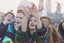 Young women laughing and taking selfie at rooftop party — Stockfoto