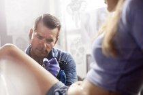 Tatuaggio focalizzato artista tatuaggio donna gamba in studio — Foto stock