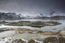 Cobertas de neve de montanhas por trás da Baía escarpada, Sund, Ilhas Lofoten, Noruega — Fotografia de Stock