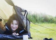 Retrato sorridente menino dentro da tenda — Fotografia de Stock