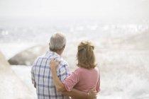 Casal mais velho abraçando na praia — Fotografia de Stock