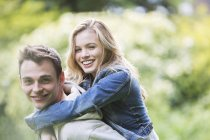 Man carrying girlfriend piggyback outdoors — Stock Photo