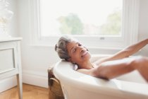 Smiling mature woman with eyes closed enjoying bath — Stock Photo