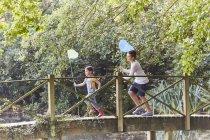 Брат и сестра бегут с бабочками по мосту в парке — стоковое фото