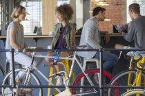Друзі гуляти говорити і пиття кави в кафе patio з велосипеди — стокове фото