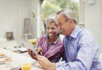 Älteres Paar Teilen digital-Tablette am Frühstückstisch lächelnd — Stockfoto