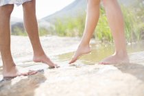 Couple dipping feet in rural pond — Stock Photo