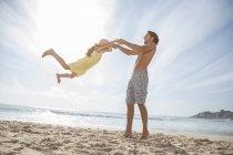 Батько і дочка, граючи на пляжі — стокове фото