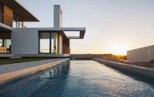 Piscina exterior de casa moderna al atardecer - foto de stock