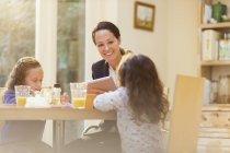 Arbeitende Mutter und Töchter am Frühstückstisch — Stockfoto