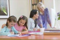 Famille de plusieurs génération à faire leurs devoirs et à l'aide d'ordinateur — Photo de stock