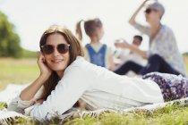 Портрет усміхається жінка покладення ковдру в Сонячний поля — стокове фото