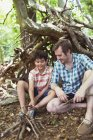 Father and son making small campfire with sticks in woods — Stock Photo
