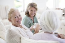 Senior women drinking coffee on sofa — Stock Photo