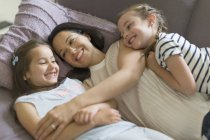 Ласкава матері і дочки обіймаються на дивані — стокове фото