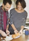 Couple buttering croissants indoors — Stock Photo