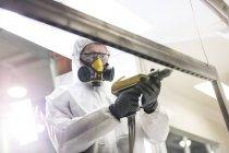 Работник в защитной рабочей одежде с помощью дрели на заводе — стоковое фото