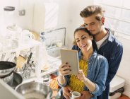 Affectionate young couple using digital tablet in apartment kitchen — Stockfoto