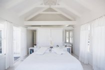 Rafters above bed in white bedroom — Stock Photo