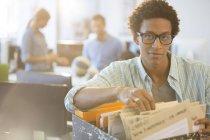 Homme d'affaires triant les fichiers dans le bureau — Photo de stock