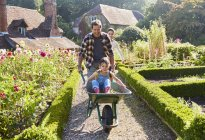 Father pushing daughter in wheelbarrow in sunny garden — Stock Photo