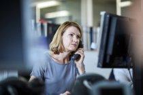 Imprenditrice che parla al telefono e lavora al computer — Foto stock