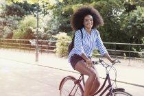 Portrait femme souriante avec afro équitation vélo dans le parc — Photo de stock