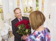 Зрелый мужчина дарит жене букет роз — стоковое фото