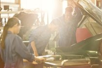 Mechanics looking inside trunk in auto repair shop — Stock Photo