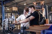 Mechanic and customer examining part in auto repair shop — Stock Photo