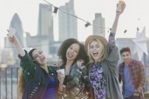 Portrait exuberant young women cheering and drinking at rooftop party — Stockfoto