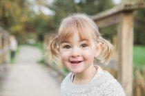 Ragazza sorridente di ritratto del bambino con le trecce — Foto stock