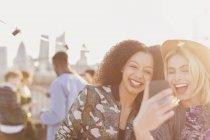 Begeisterte junge Frauen, die die Selfie auf Party auf dem Dach — Stockfoto