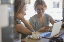 Businesswomen with coffee working at laptop in cafe — Stock Photo