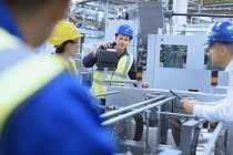 Workers talking at machinery in factory — Stock Photo