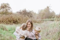 Mother and toddler children hugging in autumn park — Stock Photo