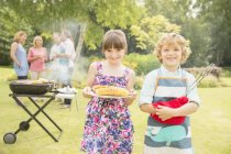 Brother and sister holding grilled corn near barbecue in backyard — Stock Photo