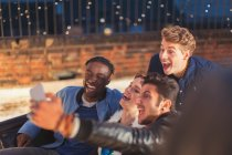 Enthusiastic young adults taking selfie at nighttime rooftop party — Stockfoto