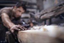 Artisan ciselant le bois en atelier — Photo de stock