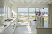 Modern white kitchen with ocean view — Stock Photo