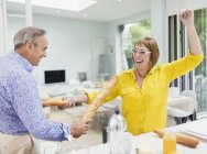 Playful mature couple sword fighting with baguettes in kitchen — Stockfoto
