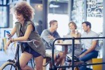 Mulher em mensagens de texto de bicicleta com celular no café — Fotografia de Stock