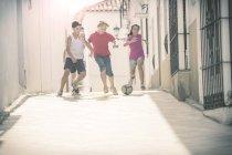 Kinder spielen mit Fußball in Gasse — Stockfoto